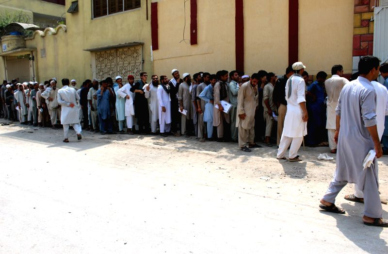 PESHAWAR, Aug. 18, 2017 - Afghan refugees wait in a queue outside a Pakistani registration centre on the outskirts of northwest Pakistan's Peshawar, Aug. 18, 2017. Pakistan on Wednesday started ...