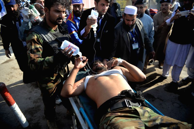 PESHAWAR, Dec. 1, 2017 - People transfer an injured soldier to a hospital in Peshawar, Pakistan, on Dec. 1, 2017. At least 12 people were injured when unknown gunmen opened fire near a hostel of a ...