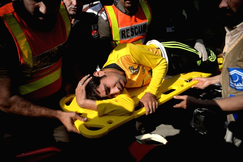 PESHAWAR, Dec. 1, 2017 - People transfer an injured man to a hospital in Peshawar, Pakistan, on Dec. 1, 2017. At least 12 people were injured when unknown gunmen opened fire near a hostel of a ...
