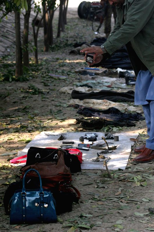 A journalist takes pictures of the belongings of victims at the attacked army-run school one day after the attack by Taliban militants in northwest Pakistan's ...