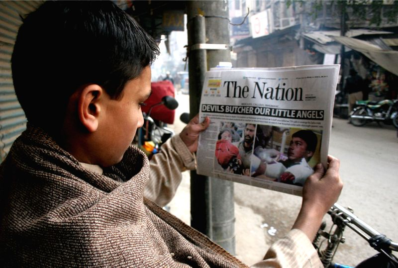 A man reads the front page of a newspaper reporting a militant attack on an army-run school in northwest Pakistan's Peshawar on Dec. 17, 2014. At least 141 people .