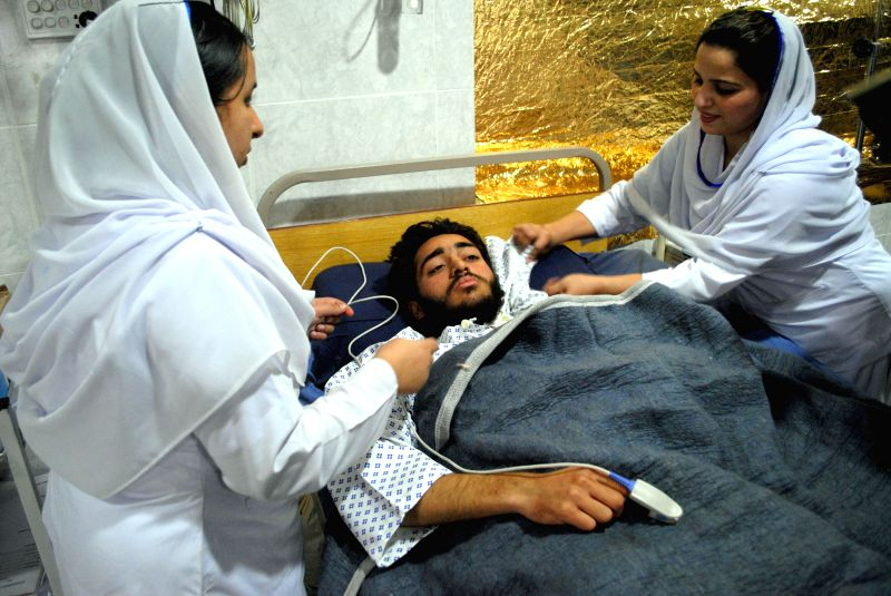 An injured student receives medical treatment at a hospital a day after an attack by Taliban militants at an army-run school in northwest Pakistan's Peshawar on ...