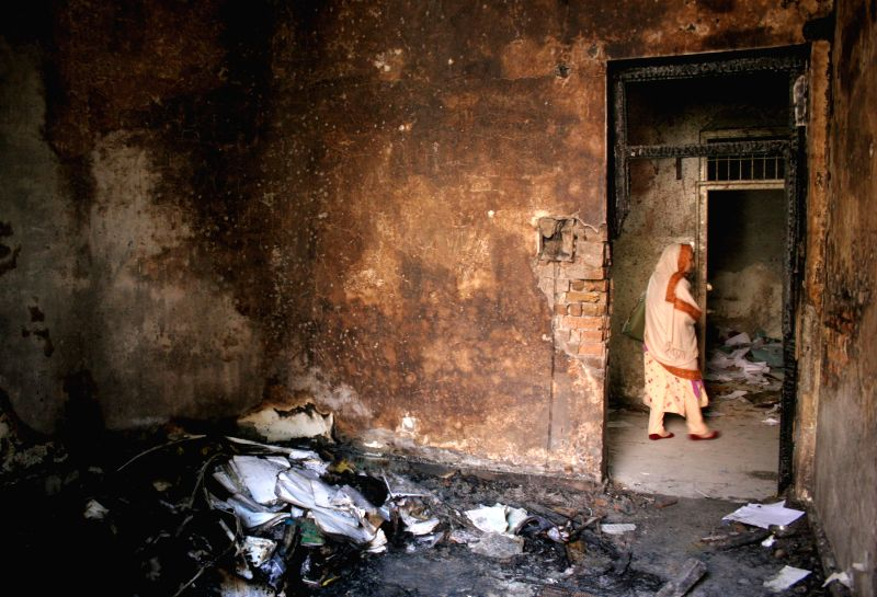 A Pakistani woman walks past a burnt classroom at the site of the militants' attack on the army-run school in northwest Pakistan's Peshawar, on Dec. 18, 2014. At ..