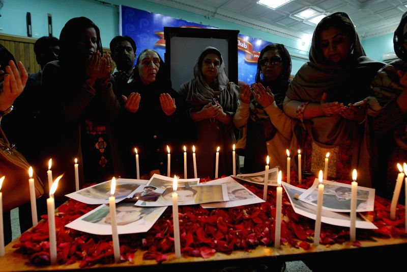 Pakistanis pay their respect to victims of the militant attack on the army-run school during a tribute ceremony in northwest Pakistan's Peshawar, on Dec. 18, 2014.