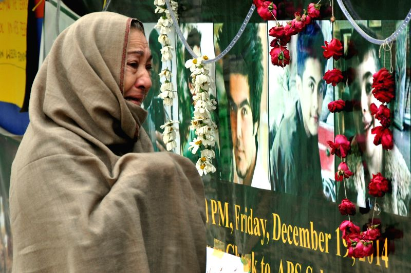 A Pakistani woman grieves on the premises of an army-run school during a memorial ceremony in northwest Pakistan's Peshawar, Dec. 22, 2014. At least 141 people, ...
