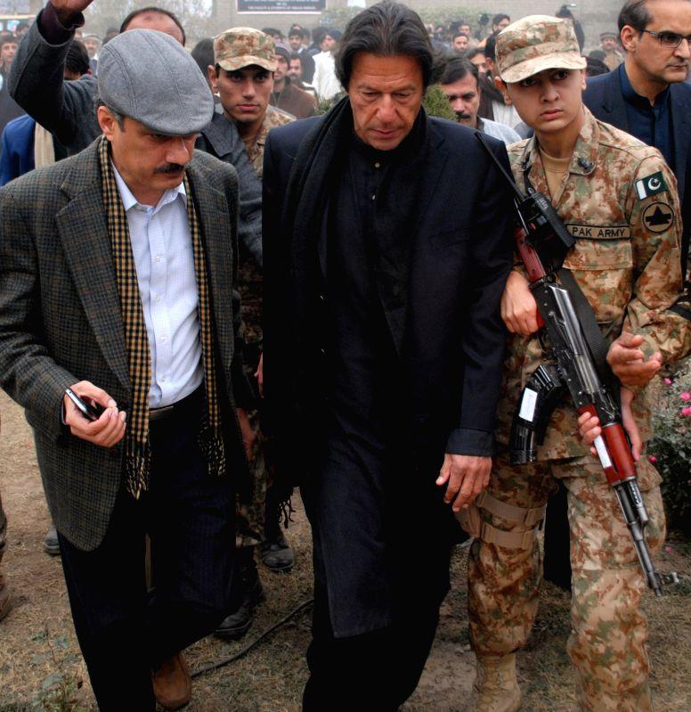 Imran Khan (C), chairman of Pakistan Tehrik-e-Insaf (PTI) political party, arrives at Army Public School during a memorial ceremony in northwest Pakistan's ... - Imran Khan