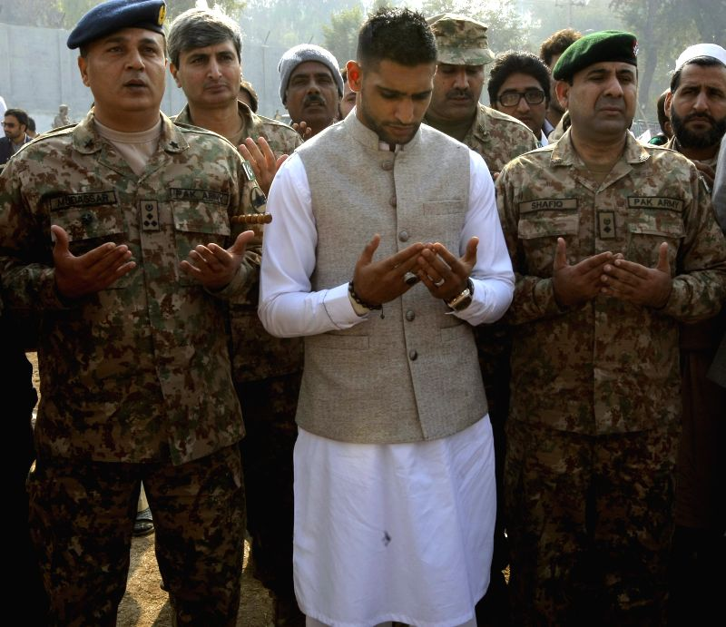 British boxer Amir Khan (C) prays with Pakistani military officials at a memorial in the army-run school where 150 people were massacred by the Taliban in ...