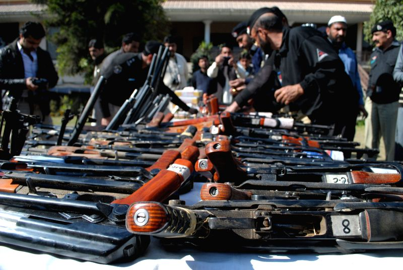 Pakistani policemen display arms and ammunition captured during an operation against terrorists in northwest Pakistan's Peshawar, Feb. 11, 2015. Police in Peshawar