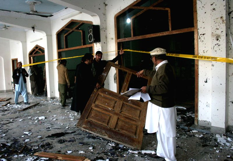 Pakistani security officials inspect the suicide blast site in northwest Pakistan's Peshawar on Feb. 13, 2015. At least 19 people were killed and over 40 others ...