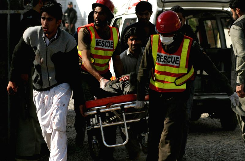 Rescuers transfer an injured man from the suicide blast site in northwest Pakistan's Peshawar on Feb. 13, 2015. At least 19 people were killed and over 40 others ..