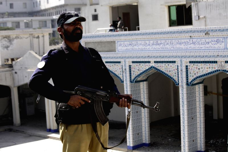 A Pakistani policeman stands guard at a Shia Muslims mosque after a militant attack in northwest Pakistan's Peshawar, Feb. 14, 2015. At least 19 people were killed