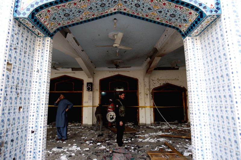 Security officials inspect the suicide blast site in northwest Pakistan's Peshawar on Feb. 13, 2015. At least 19 people were killed and over 40 others injured in a