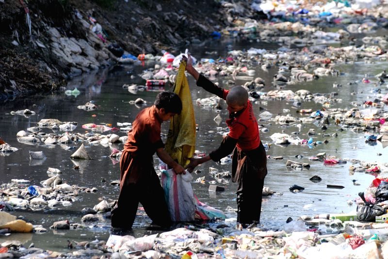 Pakistani children collect garbage from a dirty water canal on the outskirts of northwest Pakistan's Peshawar, Feb. 25, 2015.