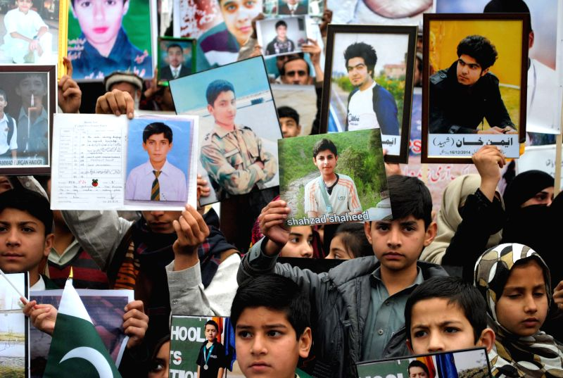 Students hold photographs of fellow students who were killed during an attack by Taliban gunmen on Army Public School (APS) during a protest in northwest Pakistan's