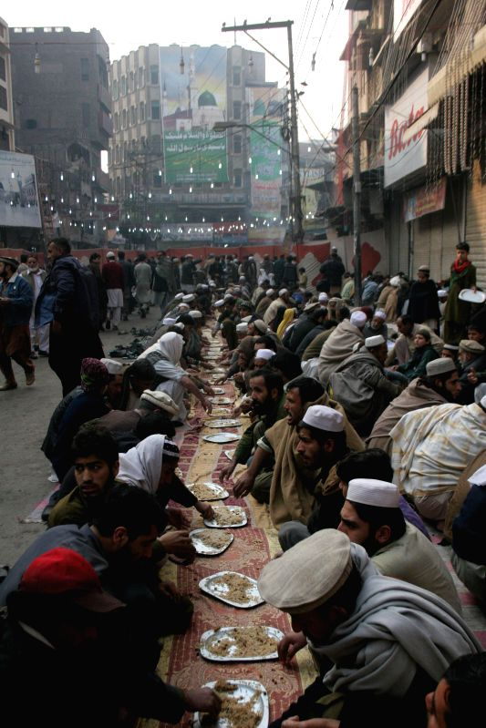 Pakistani homeless people eat food provided by charities on a street in northwest Pakistan's Peshawar, Feb. 9, 2015. If two U.S. dollars is considered to be the ...
