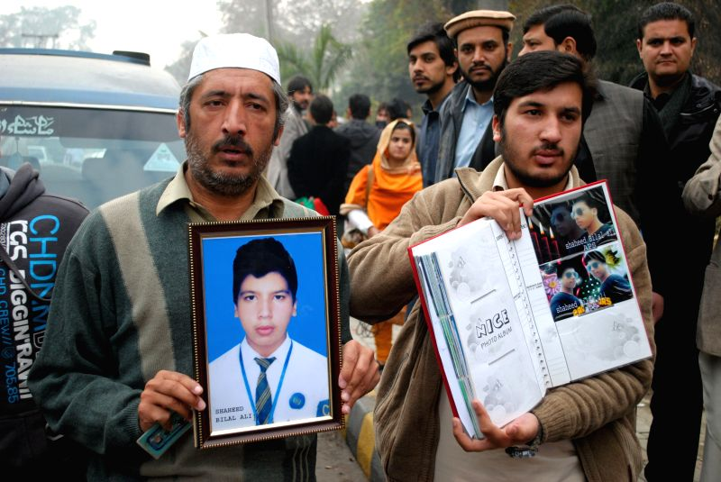 Relatives hold photographs of a student who was killed during an attack by Taliban gunmen on Army Public School (APS) during a commemoration ceremony of the ...