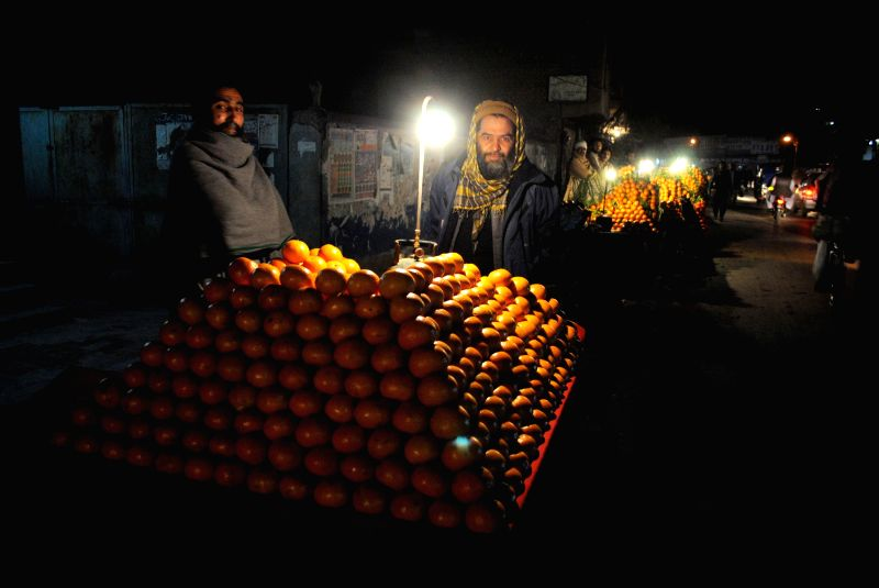 A Pakistani fruit vendor waits for customers during a power cut in northwest Pakistan's Peshawar on Jan. 25, 2015. An apparent rebel attack on a key power line ...