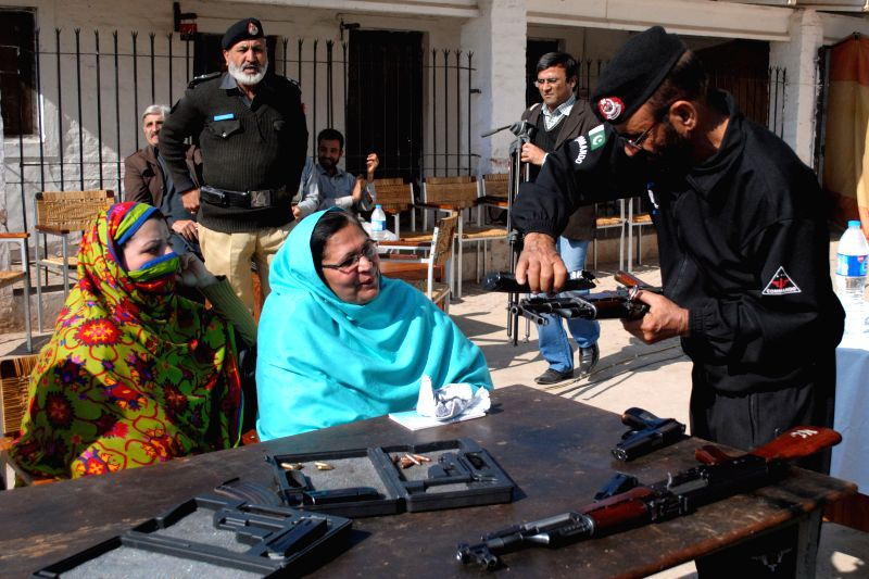 A police officer (R) gives instructions to female teachers during a weapons training session in northwest Pakistan's Peshawar on Jan. 27, 2015. A month after ...