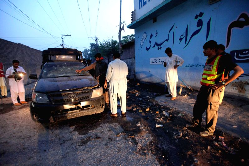 Pakistani policemen inspect a damaged vehicle at the blast site on the outskirts of northwest Pakistan's Peshawar, July 18, 2014. At least nine people including ...