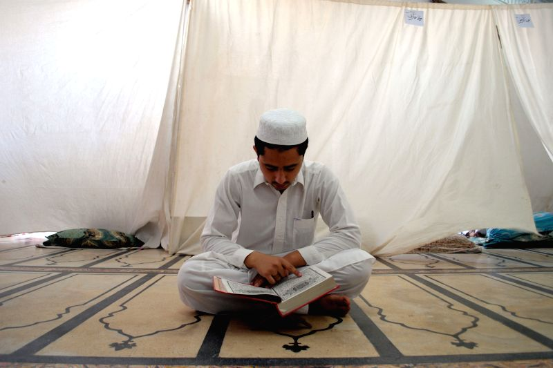 A Pakistani Muslim reads holy Koran during Itikaf at a mosque during Ramadan in northwest Pakistan's Peshawar on July 19, 2014. Itikaf is a spiritual retreat in a .