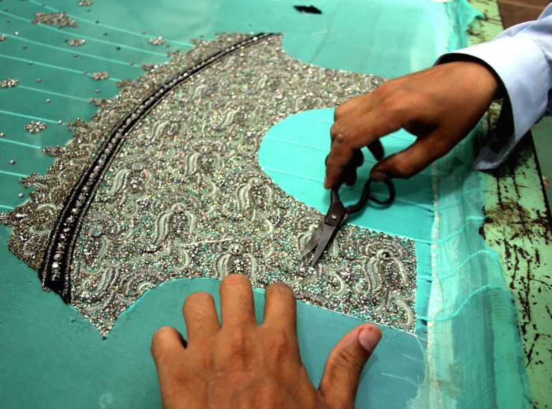 A Pakistani worker works on a handmade suit ahead of Eid ul Fitr holiday in northwest Pakistan's Peshawar on July 21, 2014.