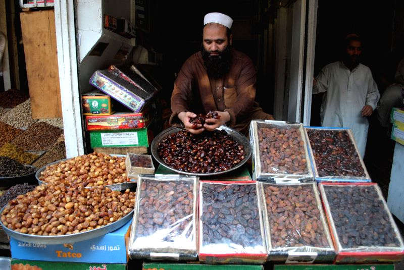 A vendor arranges dates as he waits for customers at a shop during the holy month of Ramadan in northwest Pakistan's Peshawar on July 21, 2014. Most of Pakistanis .