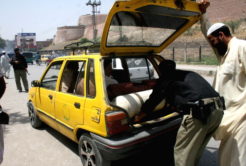 A policeman searches a vehicle on road due to security high alert in northwest Pakistan's Peshawar on June 24, 2014. Pakistan army said a suicide bomber killed two