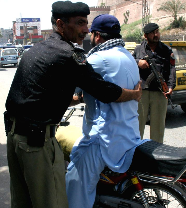 A policeman searches a motorbike rider on road due to security high alert in northwest Pakistan's Peshawar on June 24, 2014. Pakistan army said a suicide bomber ...