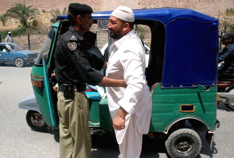 A policeman searches a man on road due to security high alert in northwest Pakistan's Peshawar on June 24, 2014. Pakistan army said a suicide bomber killed two ...