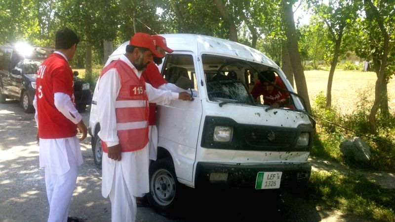 PESHAWAR, May 18, 2016 - Rescuers examine a damaged vehicle at the twin blasts site in northwest Pakistan's Peshawar, May 18, 2016. At least one policeman was killed and 14 others were injured when ...