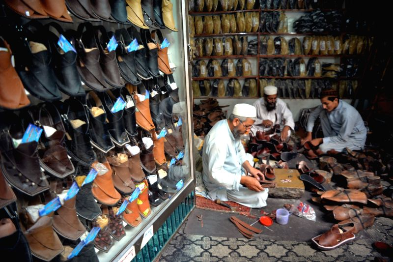 """PESHAWAR (PAKISTAN), June 13, 2018 Pakistani shoemakers make traditional shoes locally called """"chapli"""" at a workshop in Peshawar, northwest Pakistan, on June 13, 2018, in ..."""