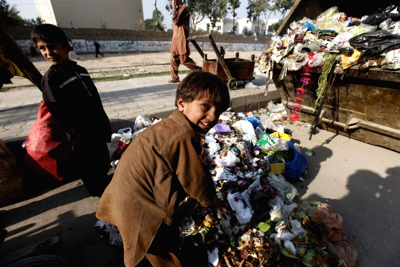 Peshawar (Pakistan): Pakistani boys collect recyclable items from garbage on Universal Children's Day in northwest Pakistan's Peshawar on Nov. 20, 2014. Universal Children's Day, which falls on Nov. .