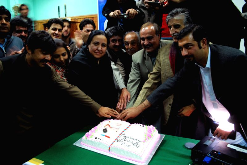 Pakistan people cut a cake as they watch a live broadcast of the award ceremony of joint Nobel Peace Prize laureate in Peshawar, Pakistan, Dec. 10, 2014. Kailash Satyarthi and Malala ... - Kailash Satyarthi