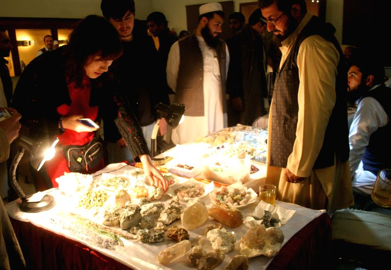 Peshawar (Pakistan):Visitors look at stones at a stall on the last day of Gems and Jewellery Exhibition in northwest Pakistan's Peshawar on Dec. 7, 2014.