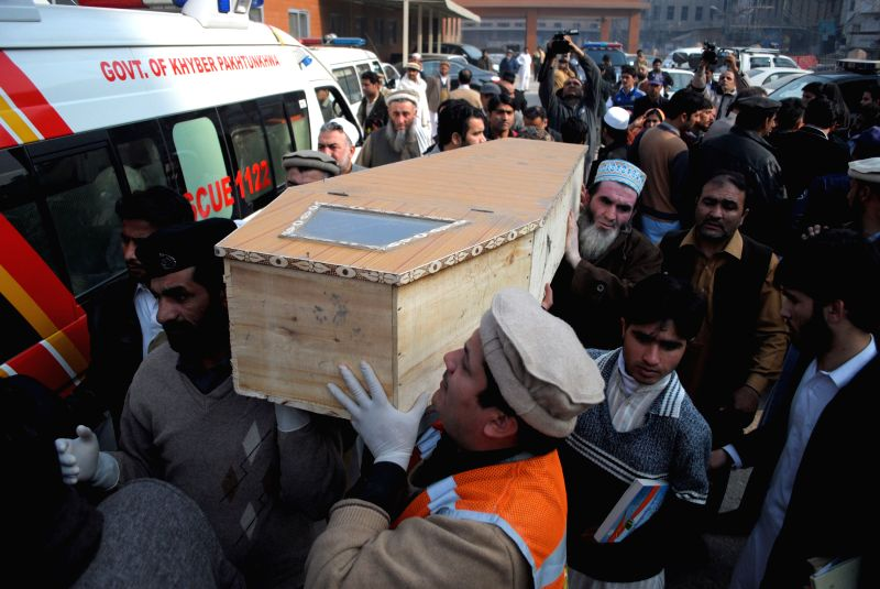 People carry a coffin of a student at a hospital in northwest Pakistan's Peshawar, Dec. 16, 2014. At least 84 people including 81 students had been killed and 83 others injured as a group ..