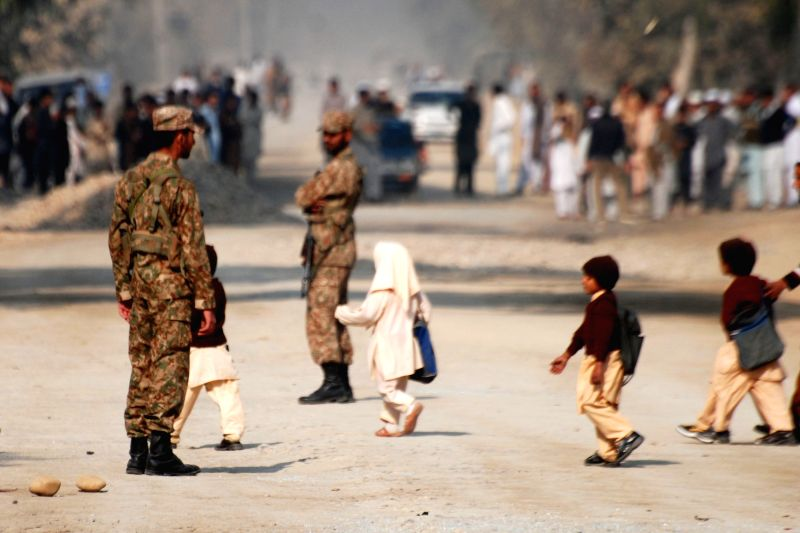 Pupils pass by soldiers who stand guard at a blast site in northwest Pakistan's Peshawar on Nov. 21, 2014. At least one security officer was killed and six others injured in a bomb attack ..