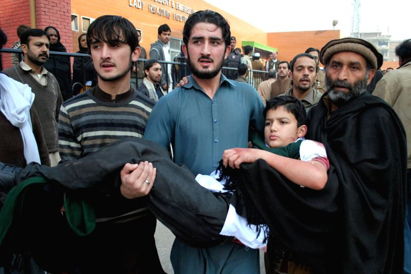 Volunteers hold an injured boy at a hospital in northwest Pakistan's Peshawar, Dec. 16, 2014. At least 84 people including 81 students had been killed and 83 others injured as a group of ...