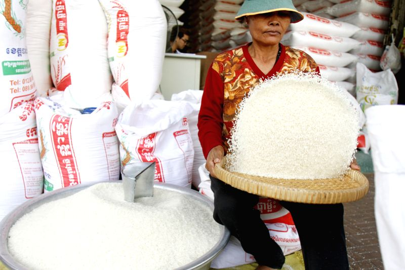 Phnom Penh: A woman cleans rice in a rice shop in Phnom Penh, Cambodia, Nov. 20, 2014. Fragrant rice from Cambodia and Thailand was awarded the world's best rice for 2014 during the 6th World Rice ...