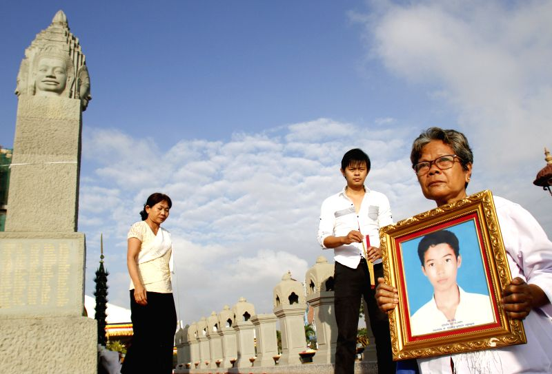 Phnom Penh: A woman holds the photo of her son who died in a Water Festival stampede four years ago, at a memorial monument in Phnom Penh, Cambodia, Nov. 22, 2014. Cambodia on Saturday held a ...