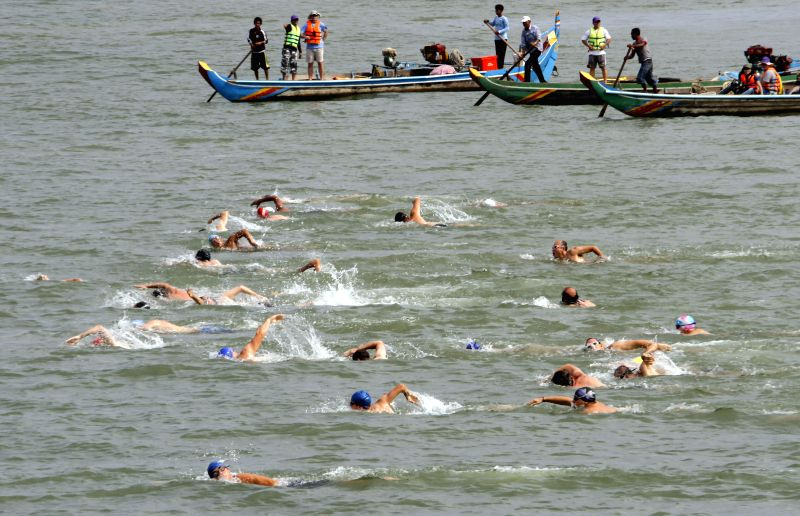 People swim in the Mekong River Swim contest in Phnom Penh, Cambodia, April 27, 2014. Approximately 140 keen swimmers, including 37 female swimmers from 20 ...