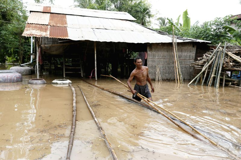 PHNOM PENH, Aug. 5 A man wades through flood waters in southern Kandal province in Cambodia on Aug. 5, 2014. Floods have hit seven Cambodian provinces along the Mekong River and Tonle Sap