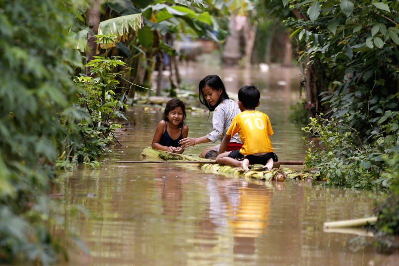 PHNOM PENH, Aug. 5 Children play in flood waters in southern Kandal province in Cambodia on Aug. 5, 2014. Floods have hit seven Cambodian provinces along the Mekong River and Tonle Sap ...
