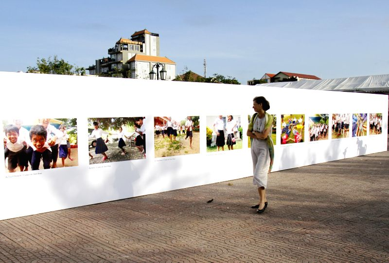 Phnom Penh (Cambodia): A woman views photos taken by children during an exhibition in Phnom Penh, Cambodia, Nov. 20, 2014. A one-month-long exhibition of children's photos kicked off here Thursday to