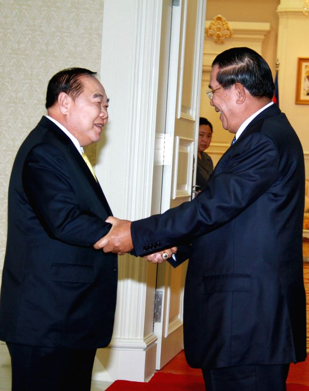 Cambodian Prime Minister Hun Sen (R) shakes hands with visiting Thai Deputy Prime Minister and Defense Minister Prawit Wongsuwan in Phnom Penh, Cambodia, Dec. ... - Hun Sen