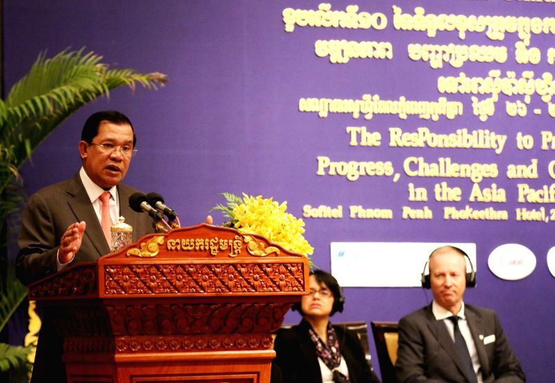 Cambodian Prime Minister Hun Sen (L) speaks during the opening ceremony of a conference in Phnom Penh, Cambodia, Feb. 26, 2015. Cambodia on Thursday hosted a ... - Hun Sen
