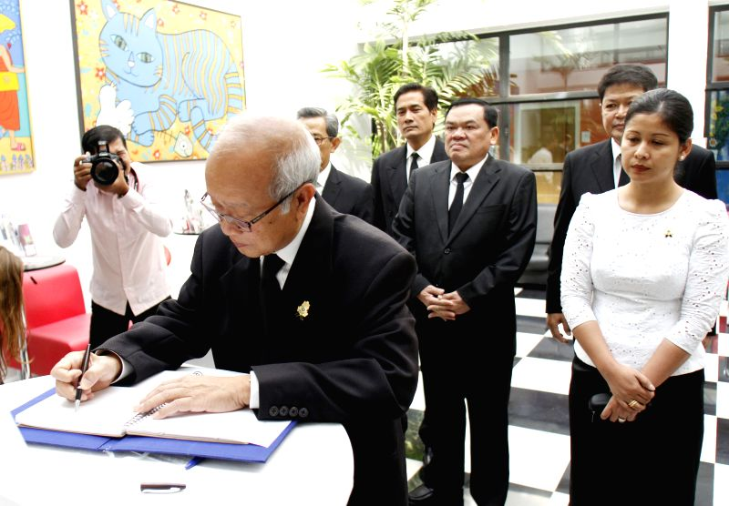 Cambodian Prince Norodom Ranariddh (front) writes in a condolence book at the French embassy in Phnom Penh, Cambodia, Jan. 12, 2015. Cambodian Prime Minister Hun - Hun Sen