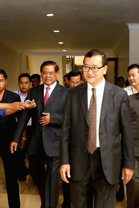 Cambodian Deputy Prime Minister Sar Kheng (front L) and Sam Rainsy (front R), president of the opposition Cambodia National Rescue Party (CNRP), leave from a ... - Sar Kheng