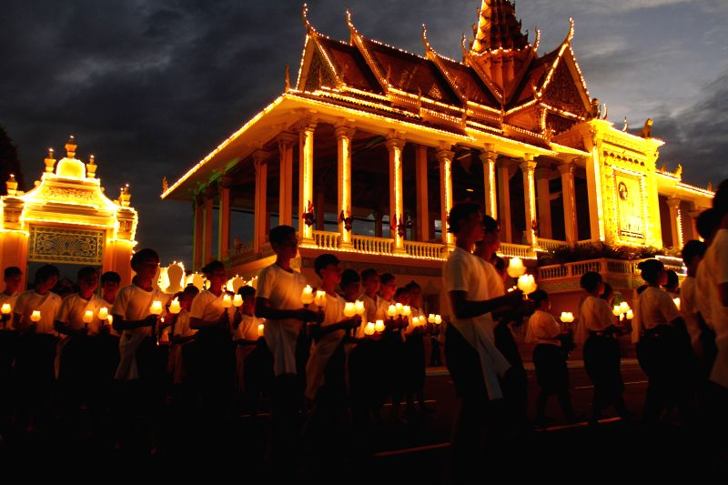 People pray in front of the Royal Palace in Phnom Penh, Cambodia, July 10, 2014. Cambodia on Thursday began a three-day elaborate ceremony to transfer the ashes .
