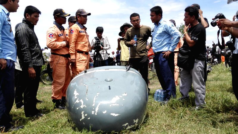 Rescuers and journalists stand beside a part of crashed military helicopter in Dangkor district on the outskirts of Phnom Penh, Cambodia, July 14, 2014. A ...