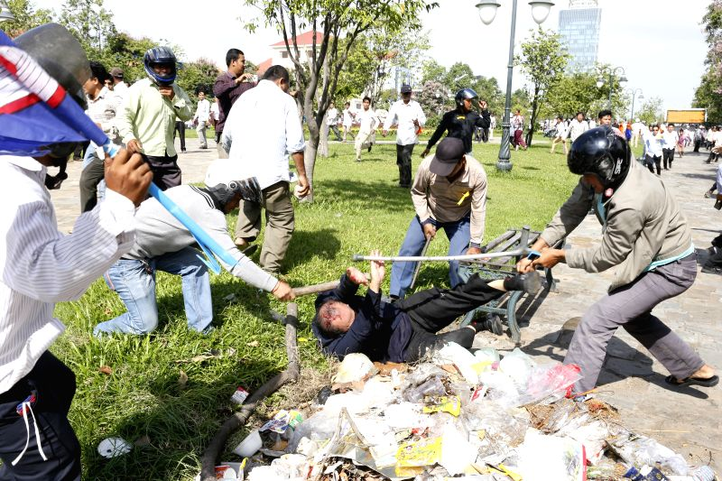 Cambodian opposition protesters beat a security guard during a protest near the Freedom Park in Phnom Penh, Cambodia, July 15, 2014. Cambodian authorities have ..
